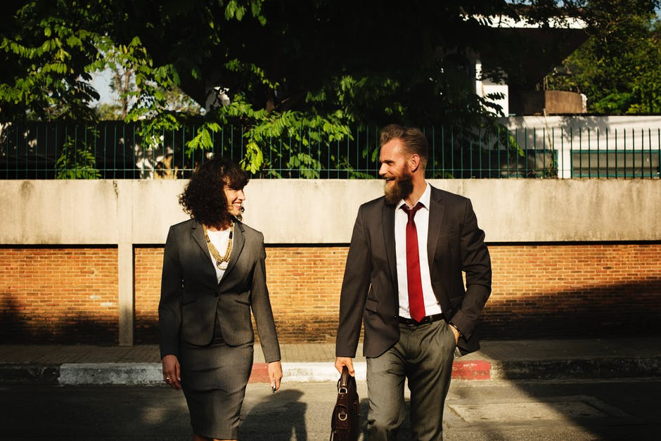 Business leader: Man and woman in suits walking